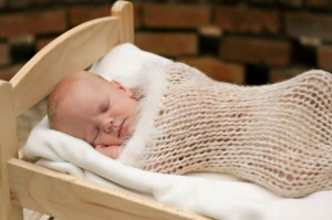 sleeping baby in knitted snuggle sack in cradle, photo credit by Earth Mama Photography